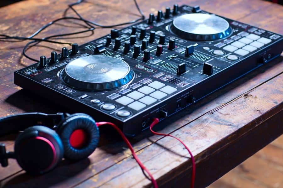 Dj mixer with headphones on wooden table close-up.